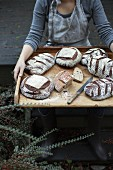 A woman presenting country bread on a wooden tray (Lummi Island, Washington, USA)