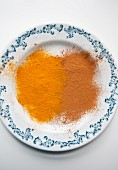 Ground cinnamon and ground turmeric on a blue and white plate
