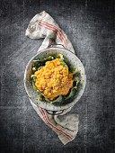 Yellow cauliflower in a colander on a linen cloth