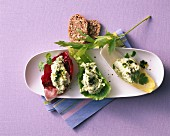 Three lettuce leaves filled with a herb dip and served with wholemeal crackers