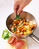 Sweet potato curry being made: leaves of fenugreek being added to diced potatoes