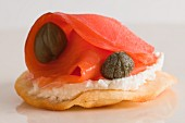 A cracker topped with cream cheese, salmon and capers (close-up)