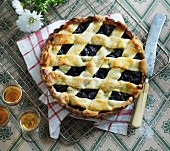 A fruit tart with dried plums and a lattice top