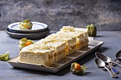 Slices of homemade mango and physalis cake on a serving platter with old teaspoons next to it