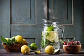 Hausgemachte Limonade im Glaskrug, Zitronen, Limetten, Minze und Kirschen auf Holztisch