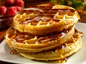 A stack of three waffles with maple syrup with raspberries in the background