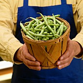A man holding a wooden basket of green beans