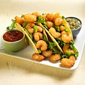 Tacos with battered prawns, tomatillo sauce and chili sauce