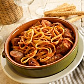 Fettuccine with sausage with marinara sauce in a ceramic bowl