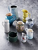 A collection of retro jugs, coloured and patterned, on a concrete floor