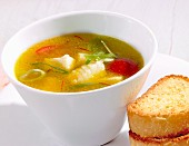 Saffron stock with fish, leek and tomatoes