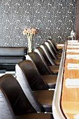 Bar counter with black leather stools in restaurant