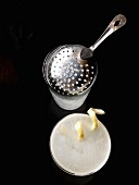 Lemon Drop cocktail with lemon zest, a shaker and bar sieve