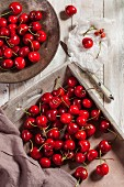 Freshly picked cherries on a wooden tray and a wooden plate
