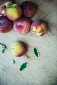 Peaches and apple mint on a wooden surface