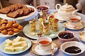 Teetisch mit verschiedenen Gerichten, Teekanne und Teetassen
