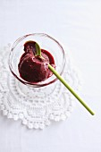 Blackberry and red wine ice cream in a glass bowl with a wooden spoon