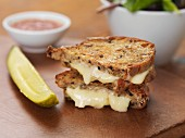 Grilled brie sandwich served with gherkin and ketchup
