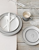 A place setting in shades of grey with plastic cutlery, a coffee cup and glasses
