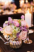 Candlestick & silver vase of roses as wedding table decoration