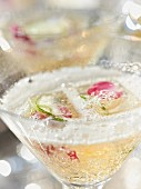 A sparkling wine cocktail with rose petals and lime
