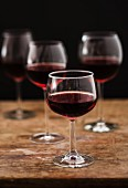 Glasses of red wine on a wooden table