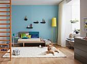 Sofa mit Ablage, davot Hund auf Teppich und Sprossenwand in Wohnzimmer mit blau getönter Wand