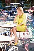 Frau in gelbem Minikleid und Jäckchen sitzt in Strassencafe