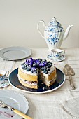 Blueberry cake with mascarpone and blueberry cream and pansies with vintage tee crockery