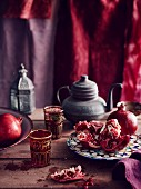 Pomegranate, tea pot and coloured glasses