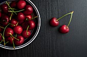 Cherries in a metal bowl on a black table