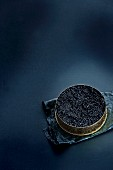 An opened tin of black caviar on a dark-blue background