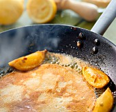 Pancakes with lemons in a pan (close-up)