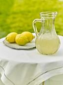 Zitronenlimonade im Krug auf Tisch im Freien