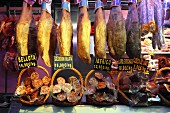 Legs of Bellota quality Iberian ham and various salamis at a market in Bilbao, Basque Country, Spain