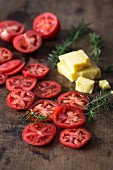 Slices of red tomatoes, pieces of cheese and fresh rosemary