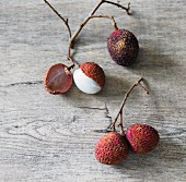 Lychees on twigs on a wooden surface