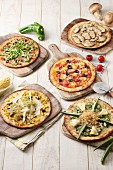 Five different vegetarian pizzas on wooden boards