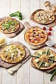Fünf verschiedene vegetarische Pizza auf Holzbrettern