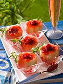 Poached white peaches filled with raspberries on a table outside