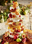 A stack of various slices of cheese, honeycomb, almonds and fruit