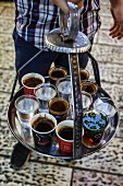 A man holding a tray of coffee, tea and water in the old city in Jerusalem, Israel