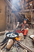 A woman from Thimphu wearing traditional clothing preparing rice in a simple wooden house in Bhutan