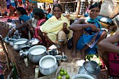 Smiling Mali tribeswomen with gold nose-rings selling yoghurt from metal pots at a weekly market at Guneipada, Orissa, India