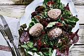 A variation of a mixed leaf salad with beetroot, preserved lingon berries and venison pâté on pumpernickel bread