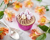 An Easter cupcake with chocolate frosting and mini chocolate eggs