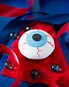 An eyeball cupcake decorated with fondant icing for Halloween