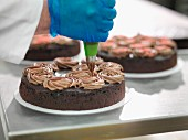 A baker decorating cake with chocolate cream in a cake factory