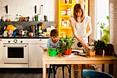 A boy and his mother with pot plants at a kitchen table