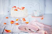 A cream cake with rose petals on a cake stand
